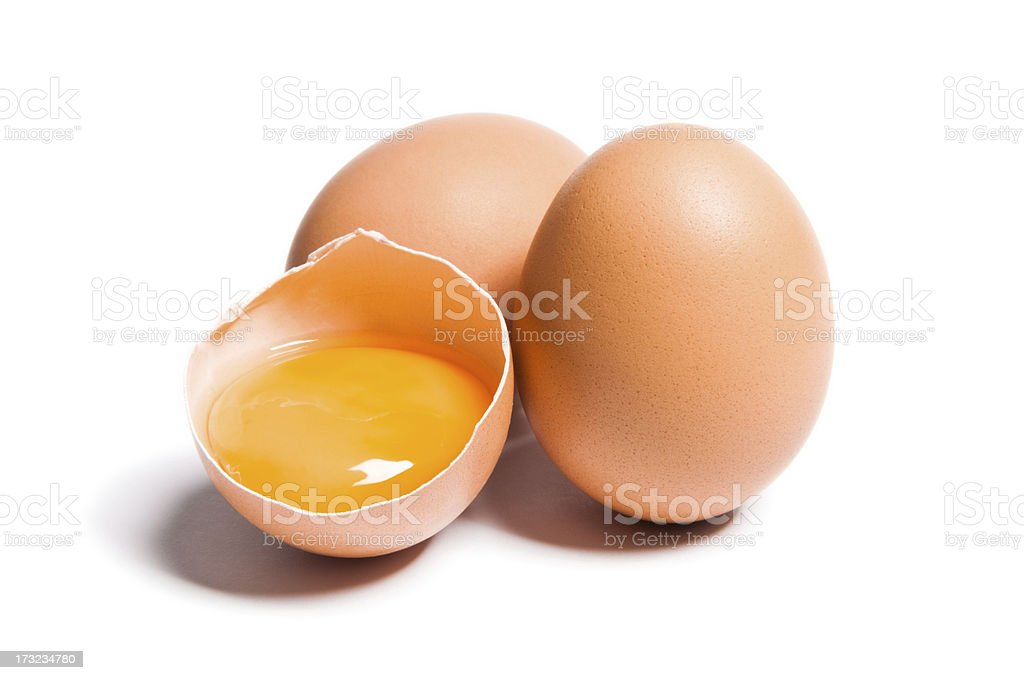 Group of brown raw eggs, one is broken, isolated white