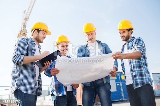 istock group of builders with tablet pc and blueprint 488715470