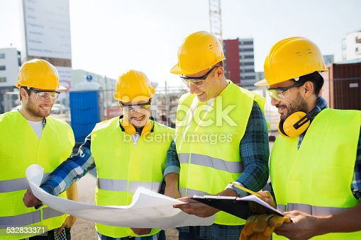 istock group of builders with tablet pc and blueprint 532833371