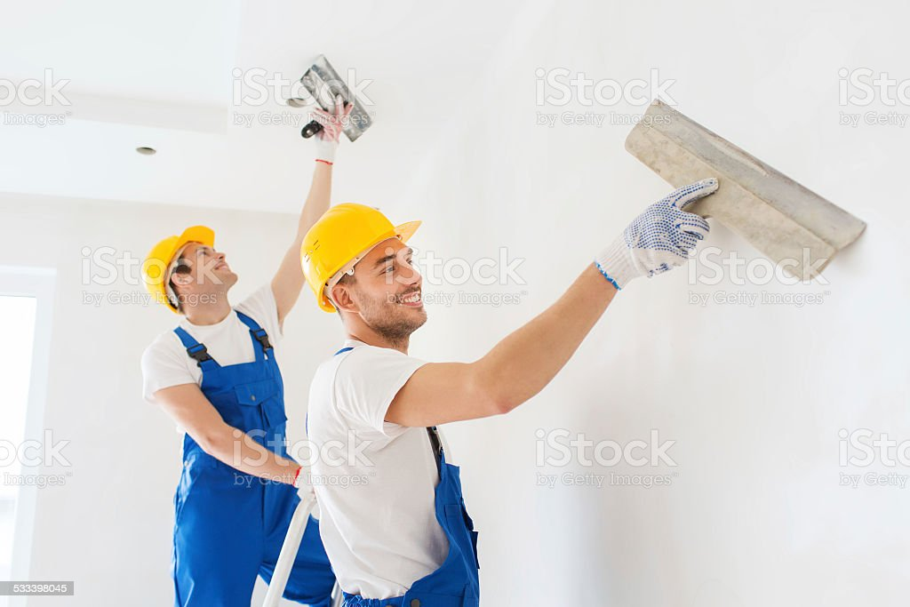 group of builders with tools indoors stock photo