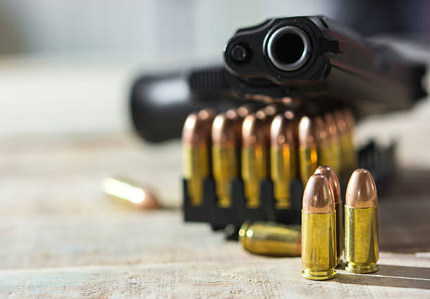Group of Bullets and  Gun on wood  background stock photo