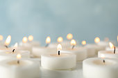 istock Group of burning candles against blue background, close up 1195555709