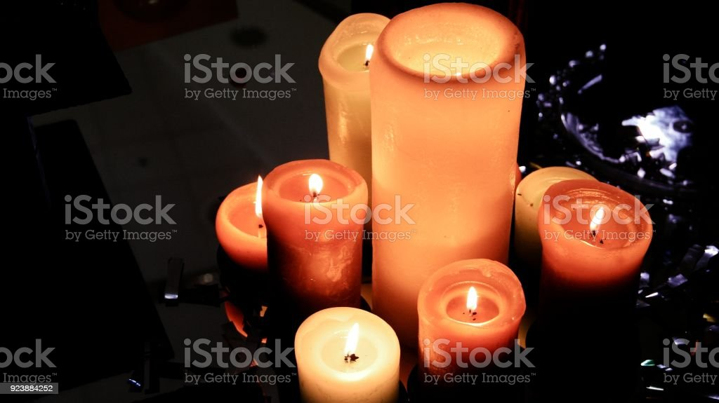Group of burning candles on table with glowing surface stock photo