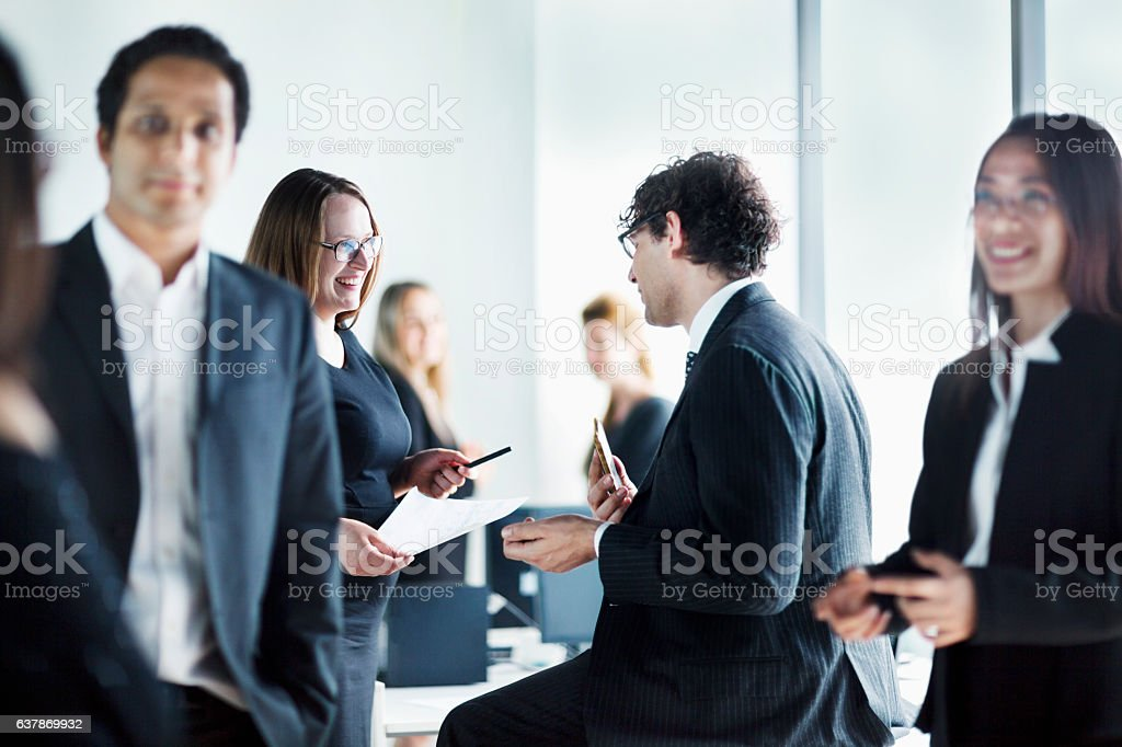 Group of business colleagues talking together in office stock photo