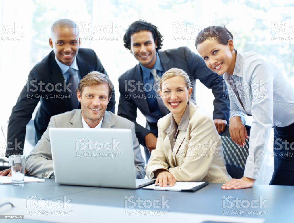 Group of business coworkers posing and smiling around laptop royalty-free stock photo