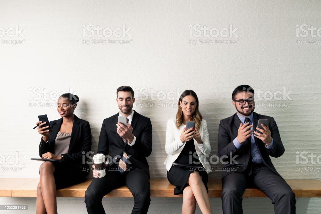 Group of business executives on their devices while waiting on bench stock photo