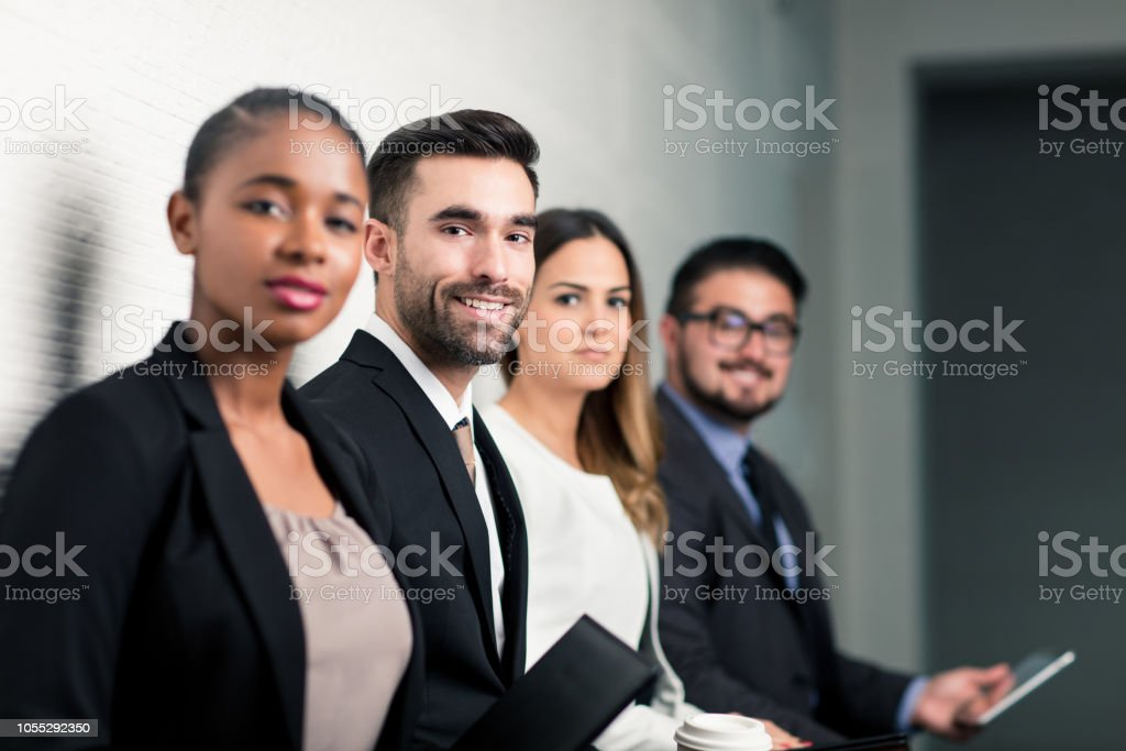 Group of business executives waiting on bench stock photo