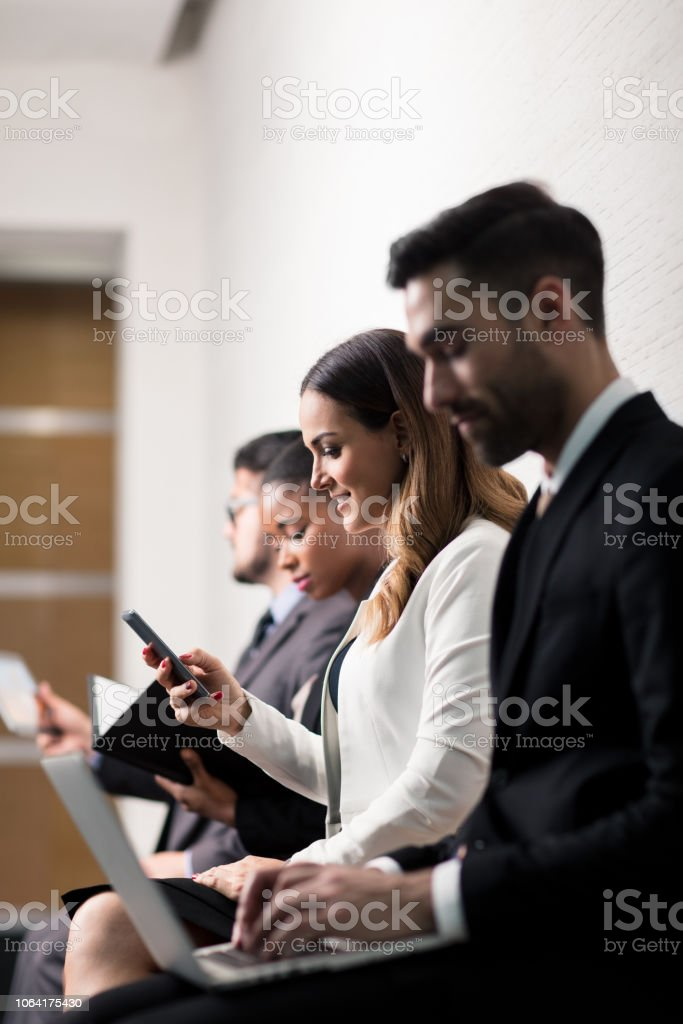 Group of business leaders sitting in waiting room stock photo
