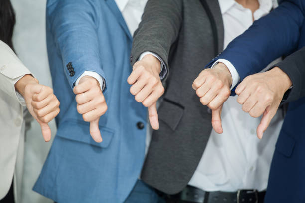 group of business manthumbs down to failing to work without a teamwork no understanding cause job failure.show dislike or unlike - thumbs down stock photos and pictures