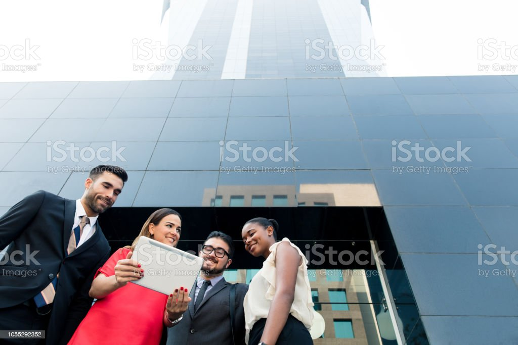 Group of business partners reading from tablet in front of building stock photo