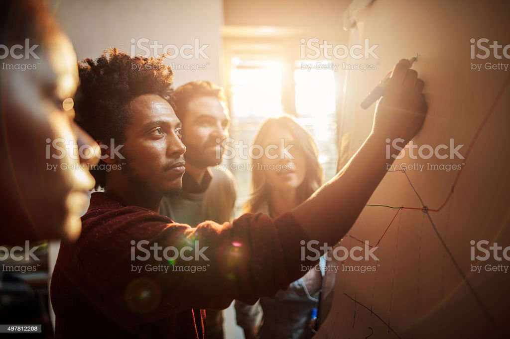 Group of business people analyzing a graph in the office. Start up team working on a business chart together. Focus is on African American man drawing. 2015 Stock Photo