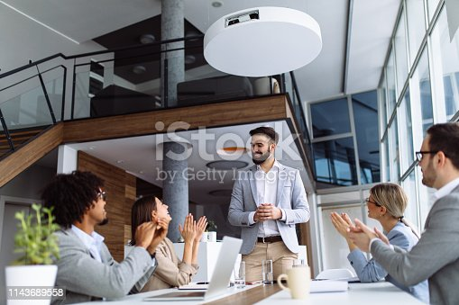 924519152 istock photo Group of business people applauding team leader after presentation 1143689558