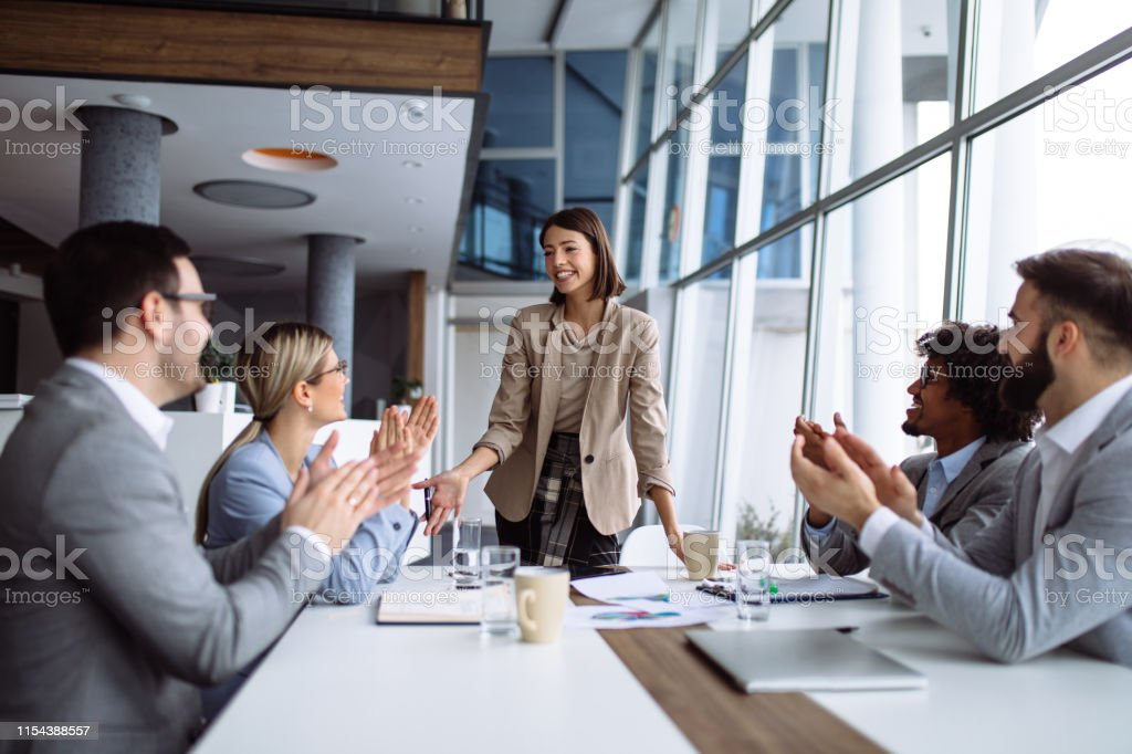 Group of business people applauding team leader after presentation