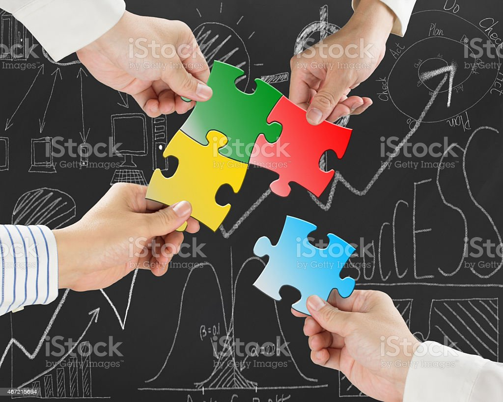 Group of business people assembling colorful jigsaw puzzles stock photo