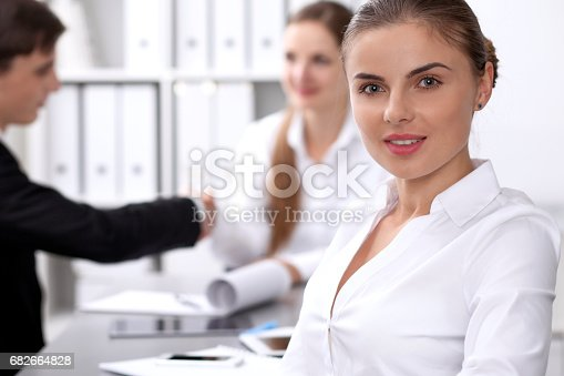 istock Group of business people at meeting on the background of office. Focus on a beautiful brunette 682664828