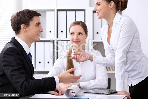 istock Group of business people at meeting on the background of office. Focus on a beautiful brunette 682664892