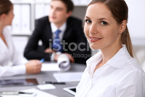 istock Group of business people at meeting on the background of office. Focus on a beautiful brunette 682689176
