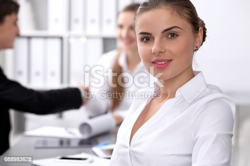 istock Group of business people at meeting on the background of office. Focus on a beautiful brunette 688983628