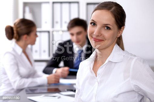istock Group of business people at meeting on the background of office. Focus on a beautiful brunette 695951130