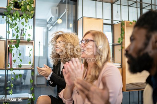 511305456 istock photo Group of business people clapping hands during seminar 1147338196