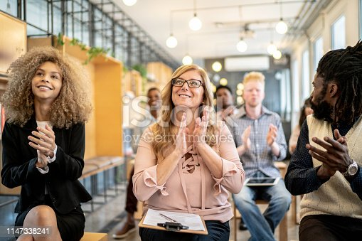 511305456 istock photo Group of business people clapping hands during seminar 1147338241