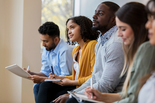 A group of business people sit in a row in a training class.  They look at an unseen speaker as they concentrate on his lecture.