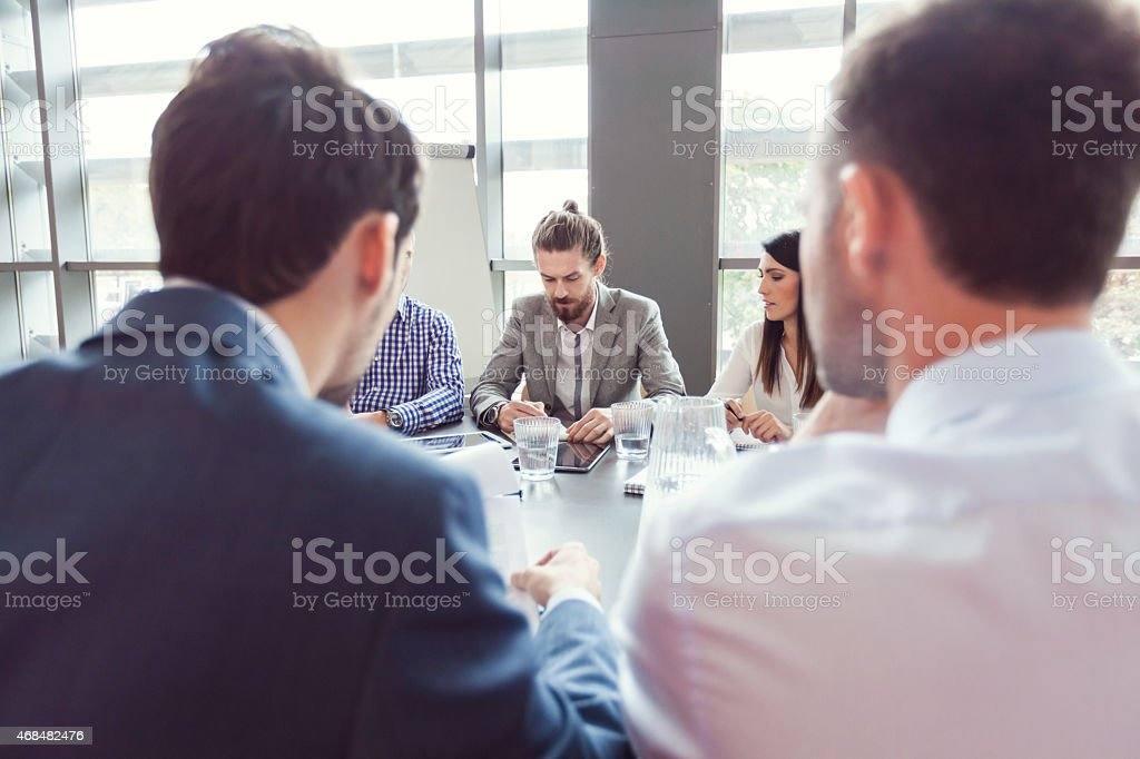 Group of business people discussing at conference table Group of business people meeting in a board room in an office, sitting at the conferecne table and discussing. Back view of two businessmen. Adult Stock Photo