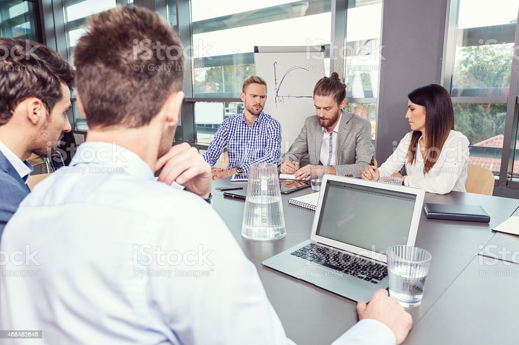 Group of business people discussing at conference table Group of business people meeting in a board room in an office, sitting at the conferecne table and discussing. On the foreground businessman using laptop. 2015 Stock Photo
