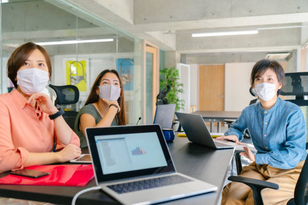 Group of business people doing business meeting while wearing protective face masks stock photo