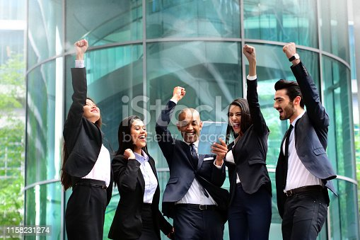 A group of business people from different ethnic backgrounds rejoices and celebrates their success in the financial and economic fields. Concept of: team work, internationality and success.