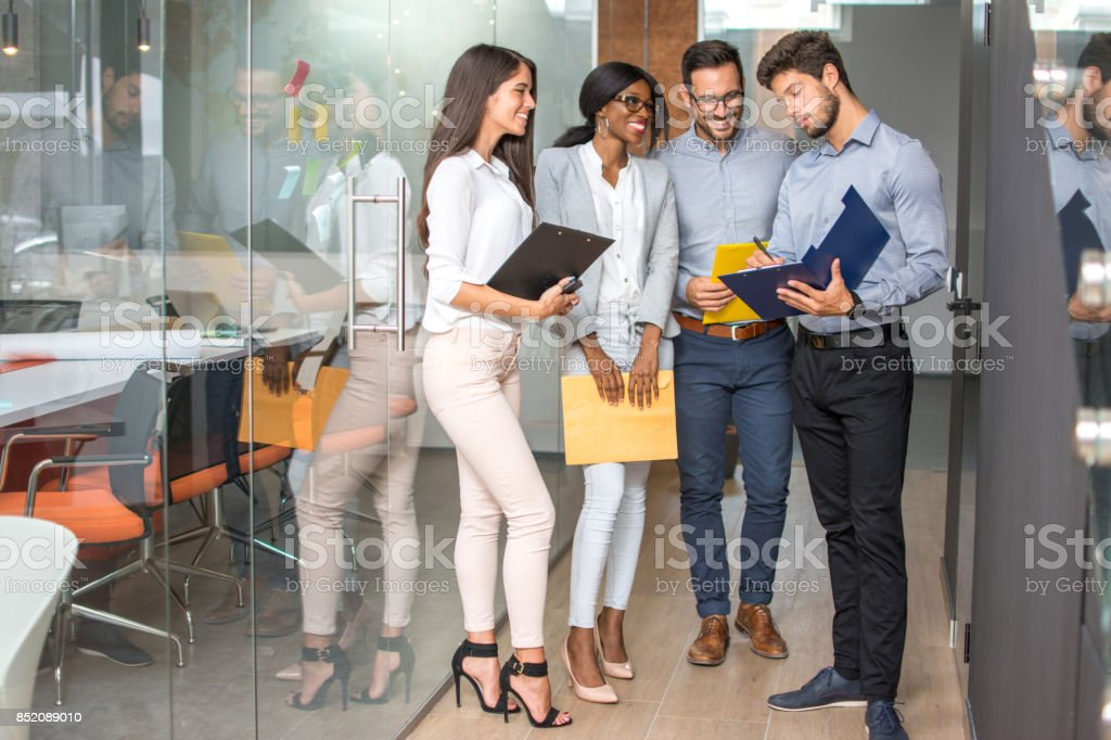 Group of business people going through paperwork in office hall. stock photo
