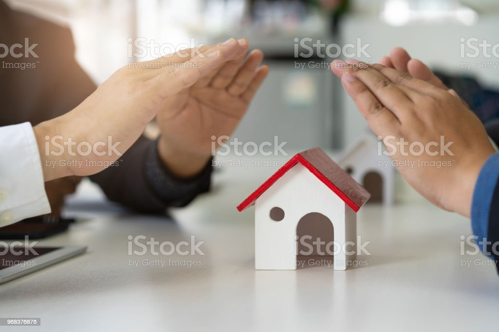 Group of business people hands protecting home.Home insurance and house protection concept. stock photo