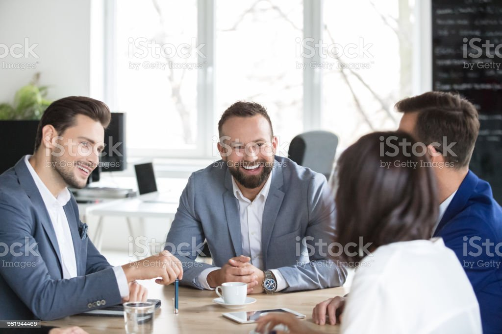 Group of business people having a meeting Group of business people meeting around table in office. Team of professionals discussing over new project in boardroom and smiling. Adult Stock Photo