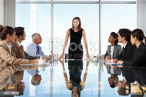 Group Of Business People Having Board Meeting Around Glass Table.