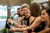 Happy group of business people having drinks at a bar and laughing – lifestyle concepts