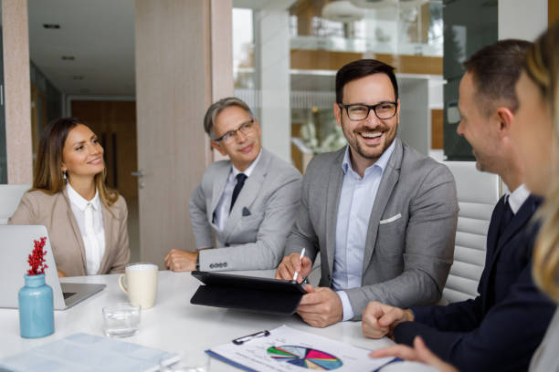 Group of business people having meeting around tablet computer stock photo