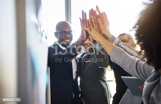 istock Group of business people high five looking positive 688060700