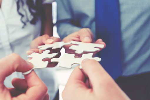 istock Group of business people holding a jigsaw puzzle pieces. 840678292