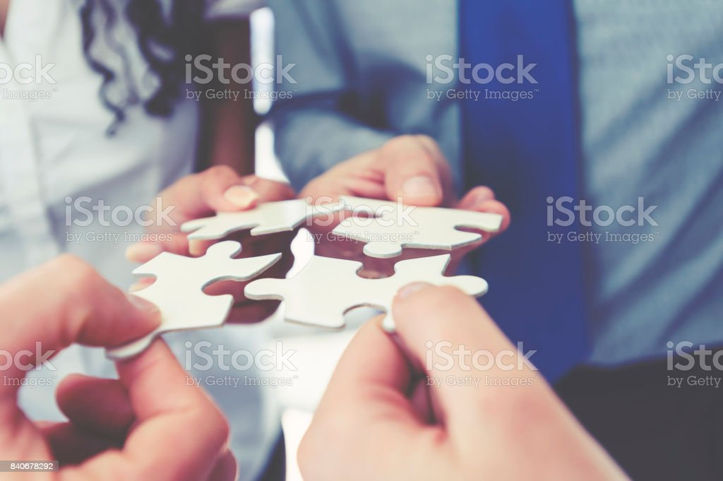 Group of business people holding a jigsaw puzzle pieces. stock photo