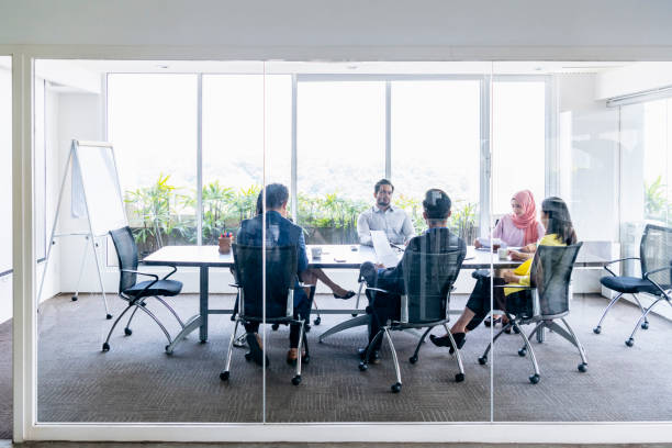 Group of business people in office meeting behind glass Multi racial businessmen and women sitting on chairs around meeting table and discussing business Malaysia stock pictures, royalty-free photos & images