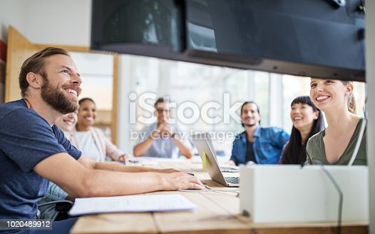 Group of business people in video conference meeting. Multi-ethnic business people having discussion in board room.