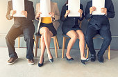 istock Group of business people is sitting in a row in an office lobby and waiting for the job interview. 1054664930