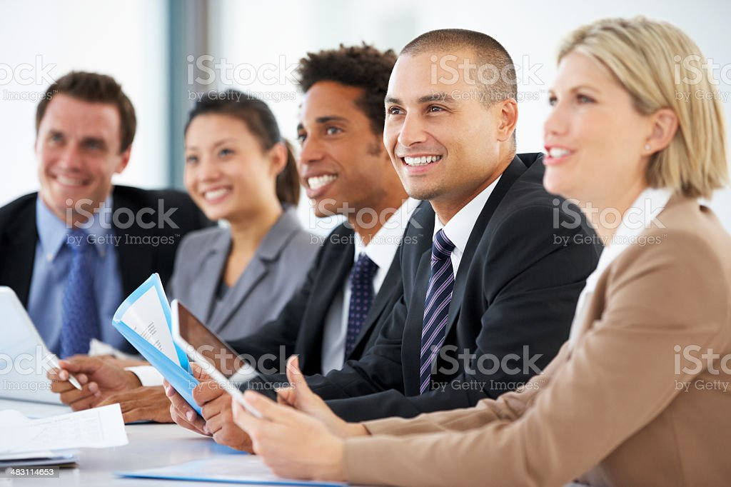 Group Of Business People Listening To Colleague Addressing Offic stock photo