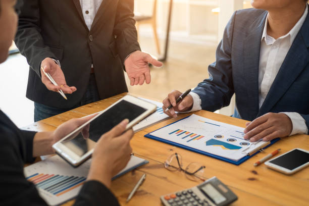 Group of business people meeting communication discussion about analyzing data financial report in office. Accounting concept. stock photo