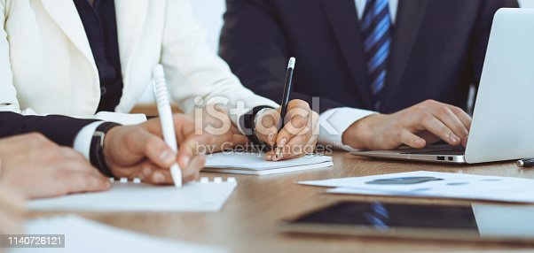 Group of business people or lawyers  work together at meeting, hands using tablet close-up. Negotiation and communication concept.