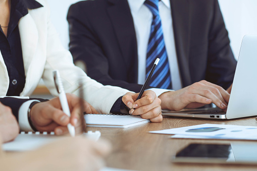 istock Group of business people or lawyers  work together at meeting in office, hands using tablet and making notes close-up. Negotiation and communication concept 1148334883