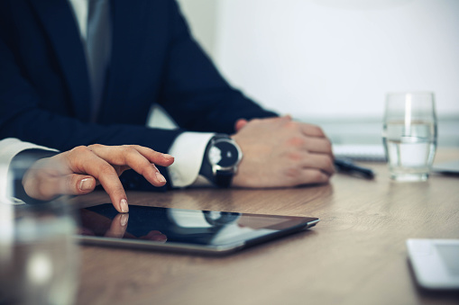 istock Group of business people or lawyers  work together at meeting in office, hands using tablet and making notes close-up. Negotiation and communication concept 1153897164