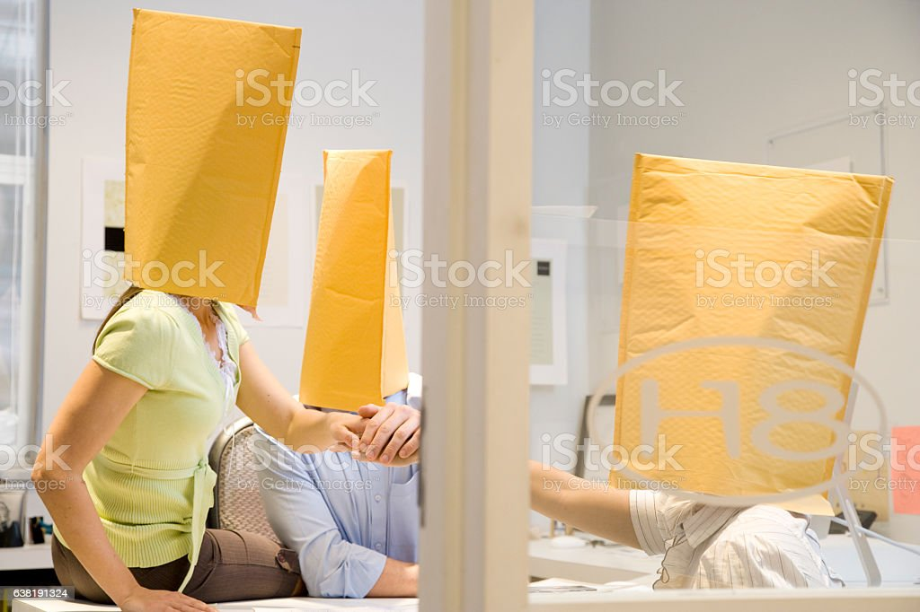 Group of business people playing with envelopes as hats stock photo