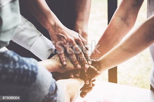 istock Group of business people putting their hands working together on wooden background in office. group support teamwork agreement concept. 875088004