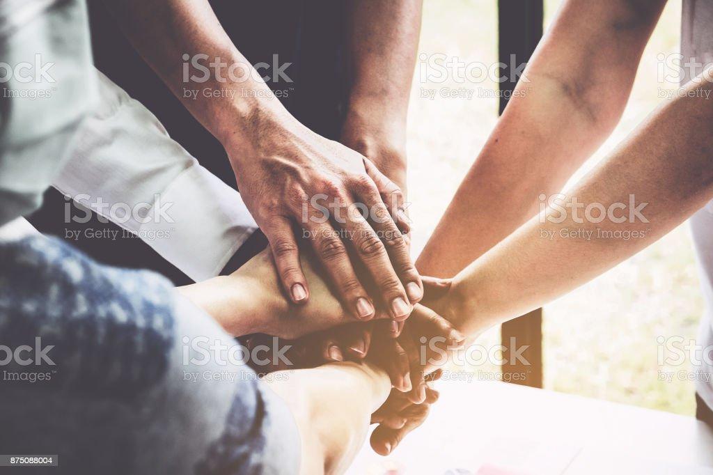 Gruppe von Geschäftsleuten, die ihre Hände auf hölzernen Hintergrund im Büro zusammenarbeiten. Support für Teamarbeit Vereinbarung Gruppenkonzept. – Foto